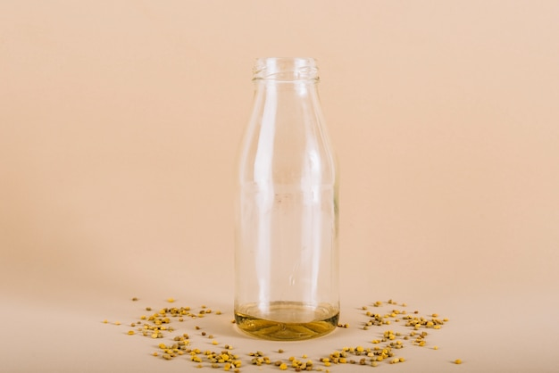 Bottle of honey with bee pollen on peach colored background
