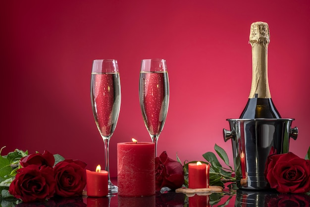 Bottle in ice bucket and beautiful glasses with sparkling wine luxurious roses on a mirror surface
