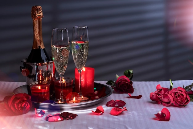 Bottle in an ice bucket glasses of sparkling wine tray with candles