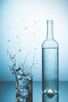 Bottle of ice water with drops, and glass of water with ice falling with splash