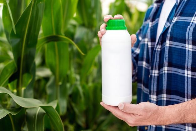 農家の手にボトル。空白のラベルなしの瓶