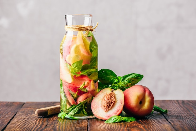 Bottle of infused water with sliced peach and basil leaves. knife and ingredients on wooden table.