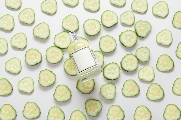 The bottle is on cucumber circles, on a white space, top view, the cucumber is spread out all over the space. concept of natural body oil