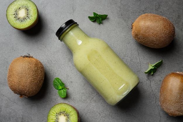 Bottiglia di succo di kiwi messa sul pavimento scuro