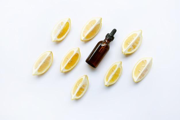 A bottle of lemon essential oil with lemons on white