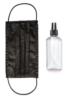 Bottle of lotion, sanitizer or liquid soap and medical protective masks over light grey background.