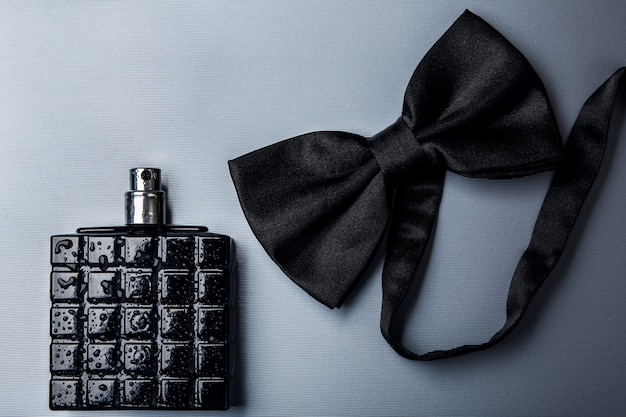 Bottle of male perfume and bow tie