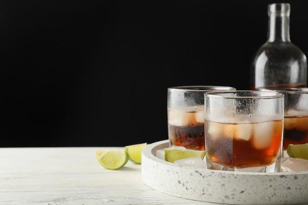 ボトル、ウイスキーとライムのグラスに白い背景の上のコピースペースの大理石トレイ