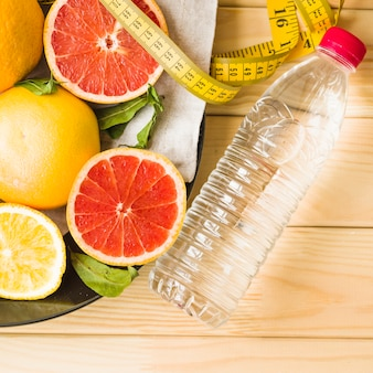 Bottle; measuring tape and citrus fruits on plate