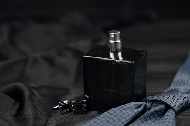 A bottle of men cologne and cufflinks with blue tie lie on a black luxury fabric