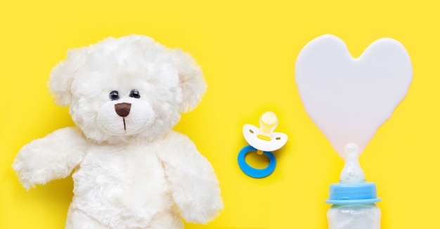 Bottle of milk for baby and baby pacifier with toy bear on yellow