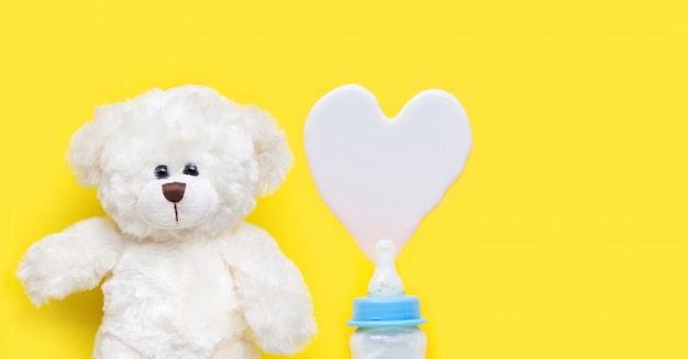 Bottle of milk for baby with toy white bear on blue background.