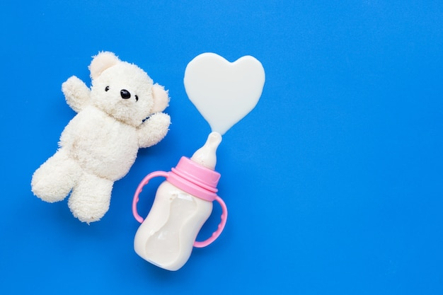 Bottle of milk for baby with toy white bear on blue