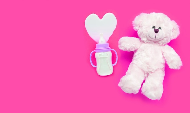 Bottle of milk for baby with toy white bear on pink surface.