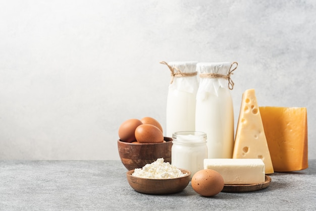 Bottle milk cheeses cottage cheese eggs yogurt and butter on table