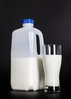 A bottle of milk and glass on a dark background.