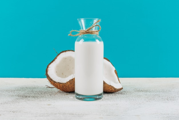 Bottle of milk with divided in half coconuts side view on a white wooden background
