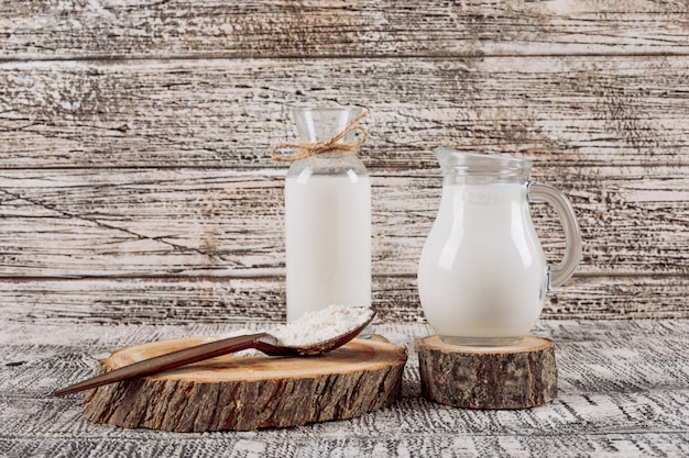 Bottle of milk with milk carafe on wooden slice, wooden spoon high angle view on a white wooden background
