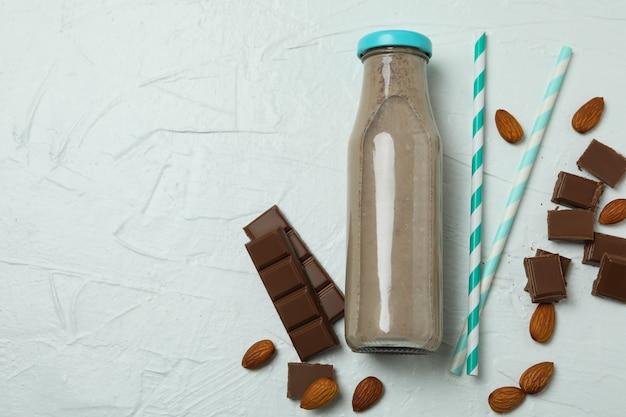 Bottle of milkshake, almond, chocolate and straws on white textured wall