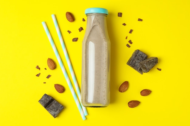 Bottle of milkshake, almond, chocolate and straws on yellow wall
