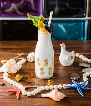 Bottle of milky shake with pipe and beach decors.