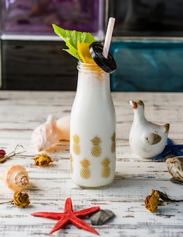 A bottle of milky shake with sea shells.