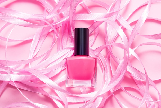 Bottle of nail polish on pink table decorated with pink ribbon