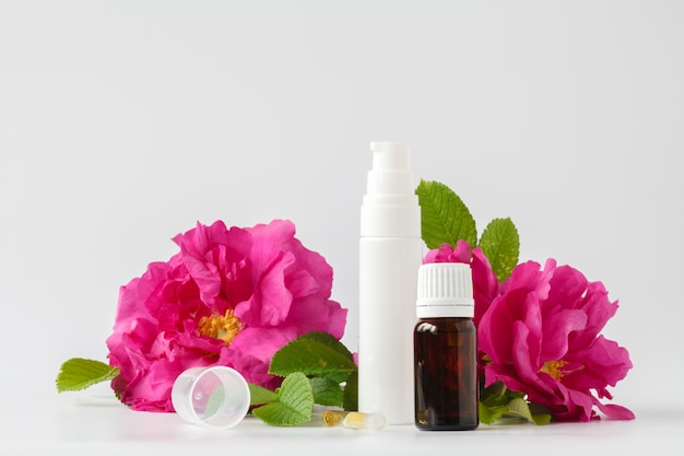 Bottle of natural wild rose oil and fresh rose flower. aromatherapy and organic skincare concept
