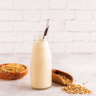 A bottle of oat milk and oats on a light background.