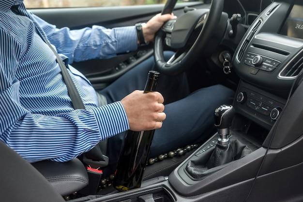 운전사 손에 있는 알코올 음료 한 병