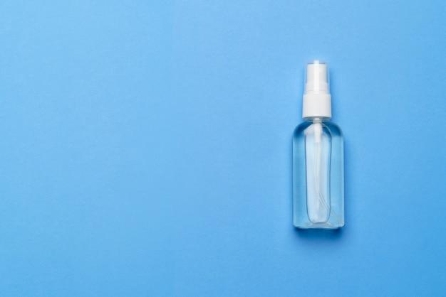 消毒用アルコールのボトルは、コロナウイルスの防止のために青色の背景にスプレーを消毒します-コピースペース付きのフラットレイアウト