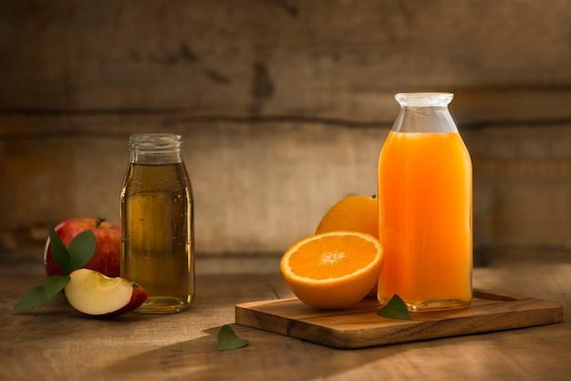 木製の背景に分離されたリンゴとオレンジ ジュースのボトル