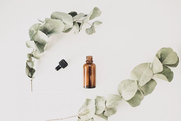 白い背景の上のユーカリの枝に囲まれた白い背景の芳香の化粧品やエッセンシャルオイルのボトル。上面図。スペースをコピーします。