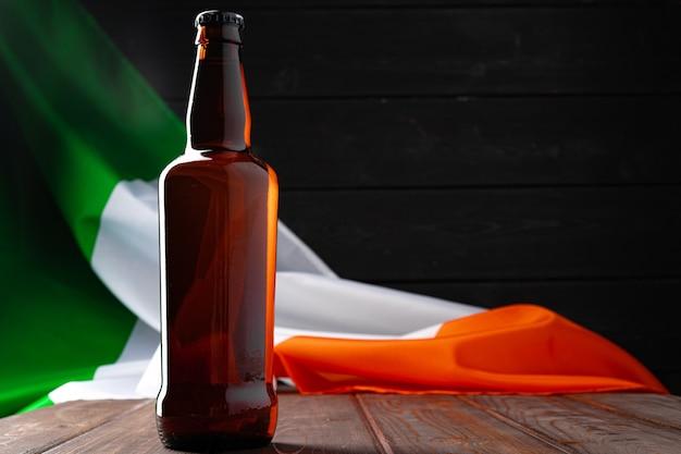アイルランドの旗に対してビールのボトルをクローズアップ