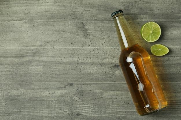 灰色のテクスチャ背景にビールとライムのボトル