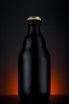 グラデーションの黒い背景の上のビールのボトル