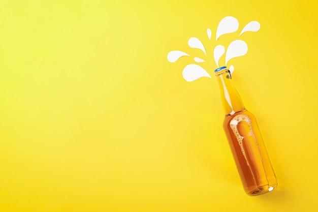 黄色、テキスト用のスペースにビールのボトル