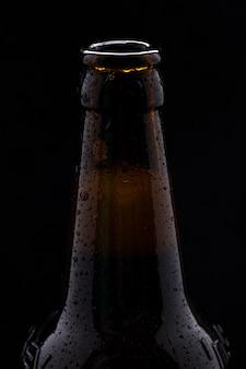 Бутылка пива с каплями воды крупным планом на черной изолированной стене