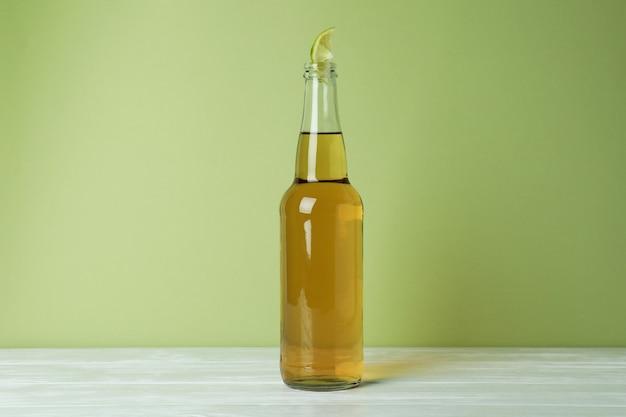 緑の背景にライム スライスとビールのボトル