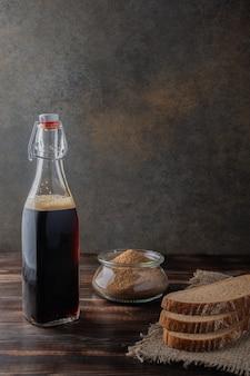 Бутылка черного пива с хлебом