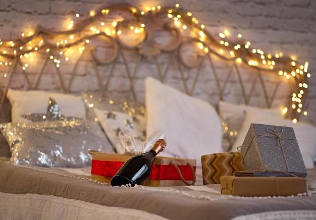 Бутылка шампанского и подарочные коробки на кровати