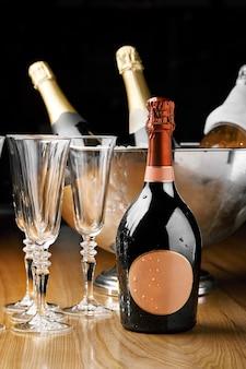 氷とシャンパンのボトルが入ったクーラーの表面にあるシャンパンのボトルとシャンパン用グラス