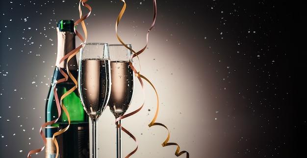 Бутылка шампанского и два наполненных бокала, концепция праздника с лентами и снежинками
