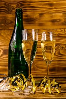 Бутылка шампанского и два бокала, украшенные золотой лентой, на деревенском деревянном столе