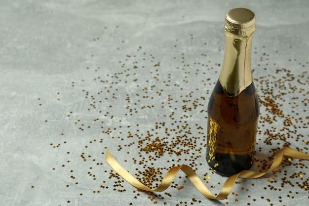 灰色のテクスチャ背景にシャンパン、キラキラとリボンのボトル。