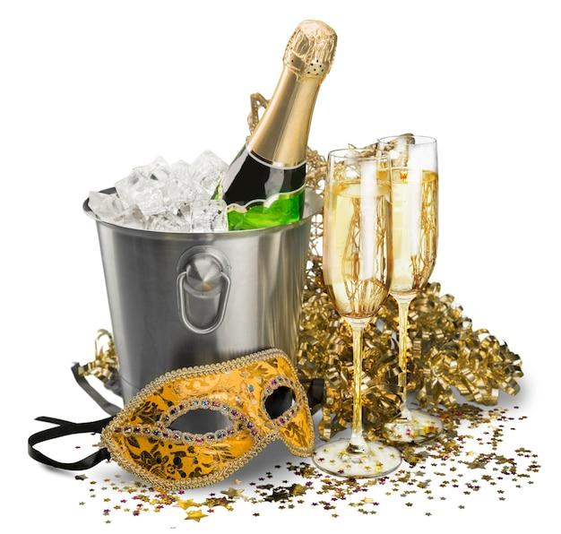 フルート、ストリーマー、マスク付きアイスバケットのシャンパンのボトル