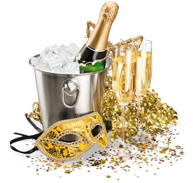 Бутылка шампанского в ведерке со льдом с флейтами, растяжками и маской