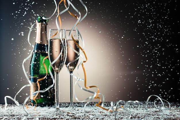 Бутылка шампанского, фужеры с серебряными и золотыми лентами, снегопад на темном фоне с подсветкой. концепция праздника