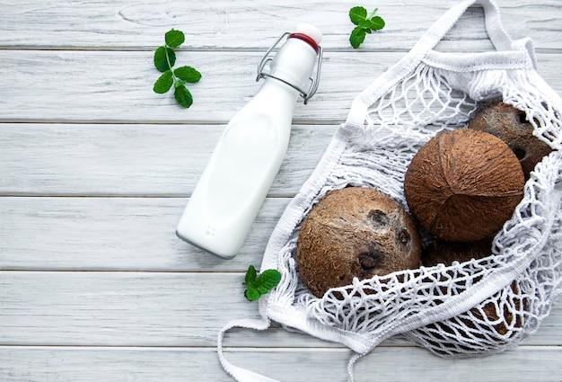 Бутылка кокосового молока и кокосов в эко сетке на деревянном столе
