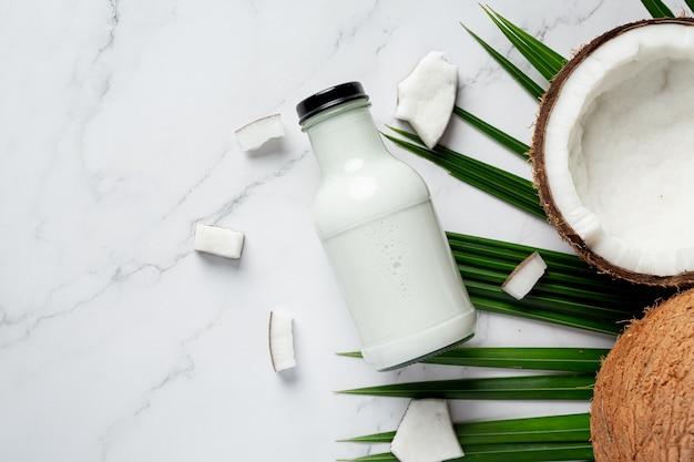 白い大理石の背景に置かれたココナッツミルクのボトル